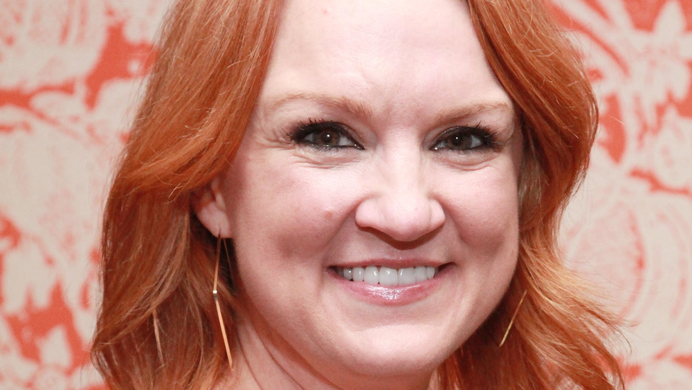 Ree Drummond smiling with a red background