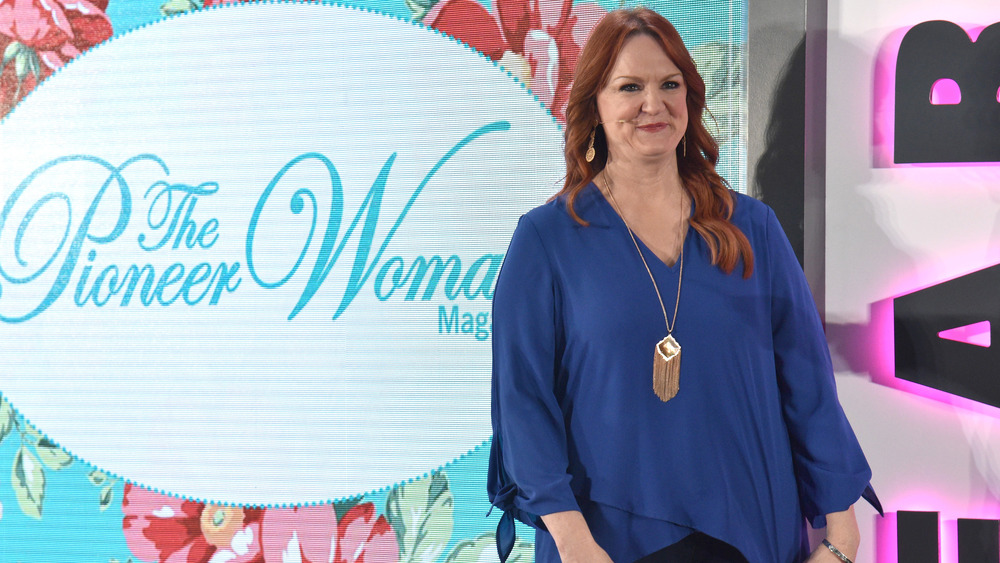 Ree Drummond in blue shirt, silver necklace, and silver bracelet standing in front of The Pioneer Woman Magazine background