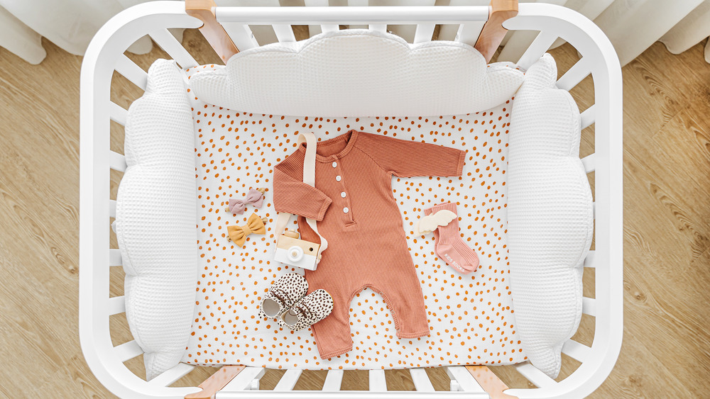 Baby clothes in a crib
