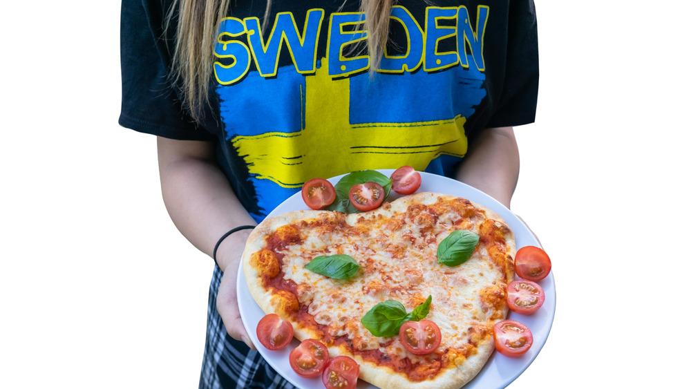 Person wearing Swedish flag t-shirt holding pizza