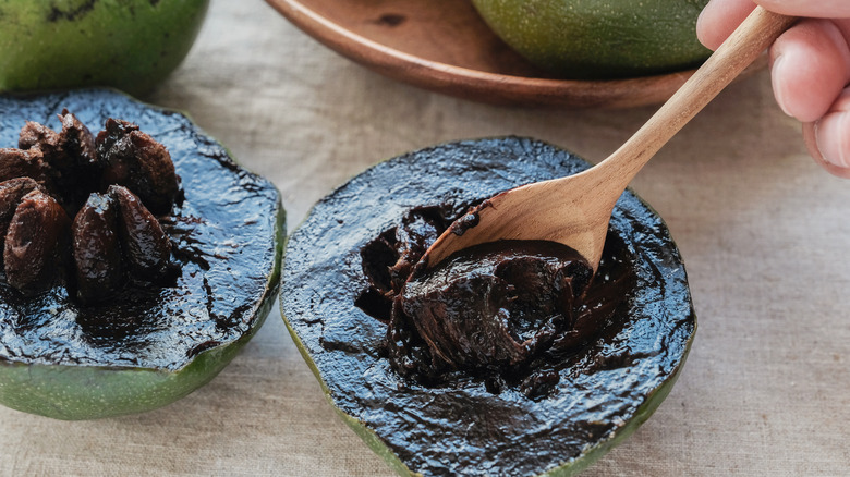 spooning out black sapote