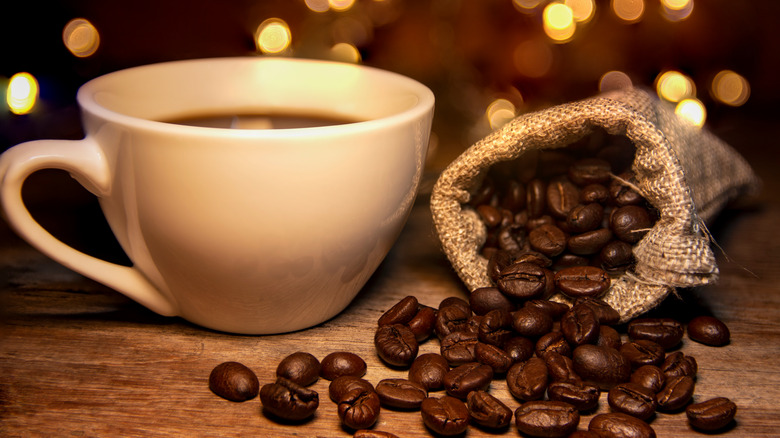 Cup of coffee and roasted coffee beans on table
