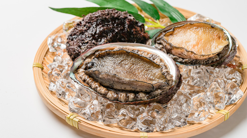 Abalone in its shell on a wooden platter