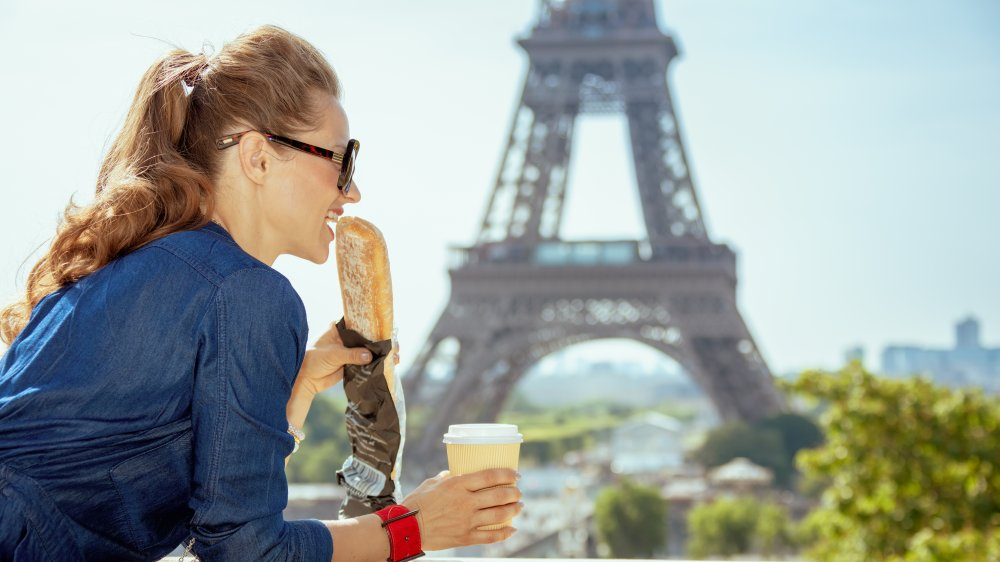 Woman eating a baguette in front of the Eiffel Tower