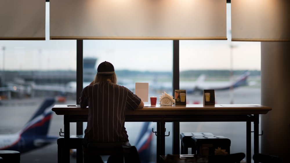 Person eating at an airport in front of window with planes outside