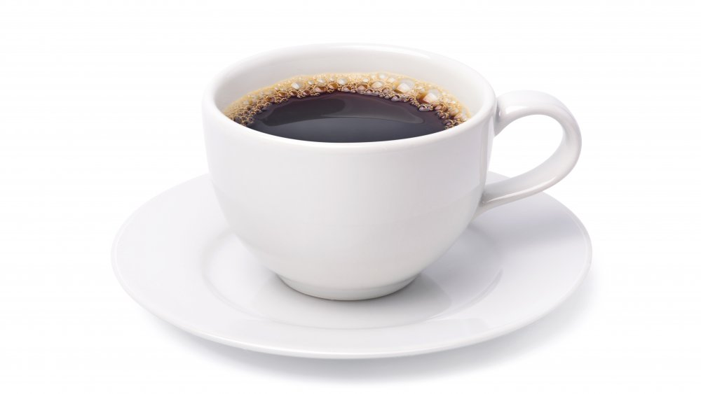Black coffee in a white cup against a white background.