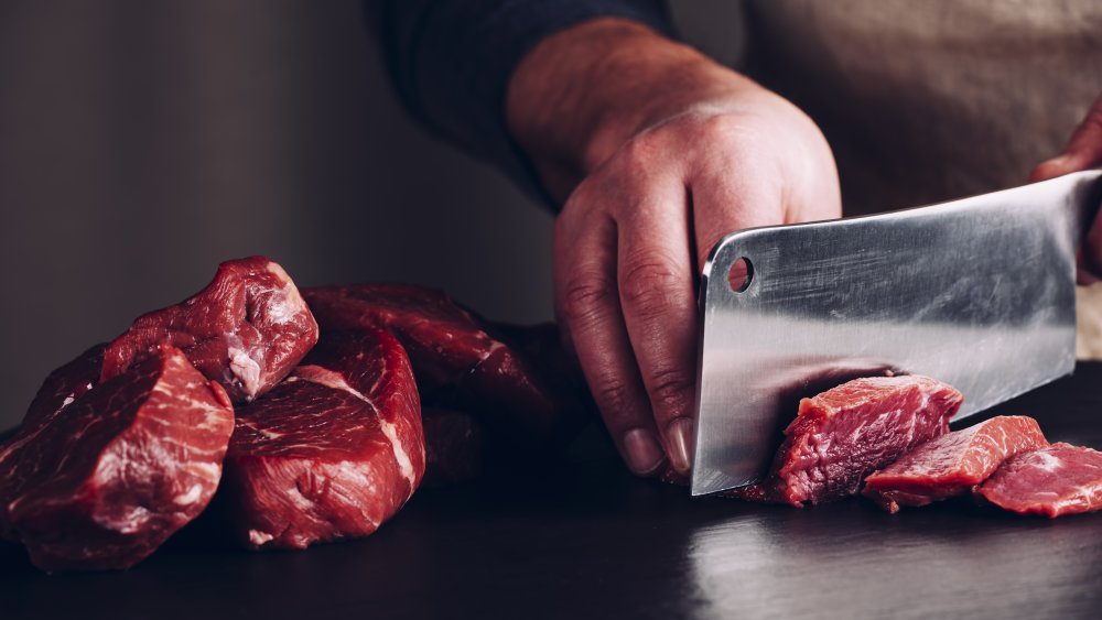 Hand of chef and butcher knife chopping up raw steak