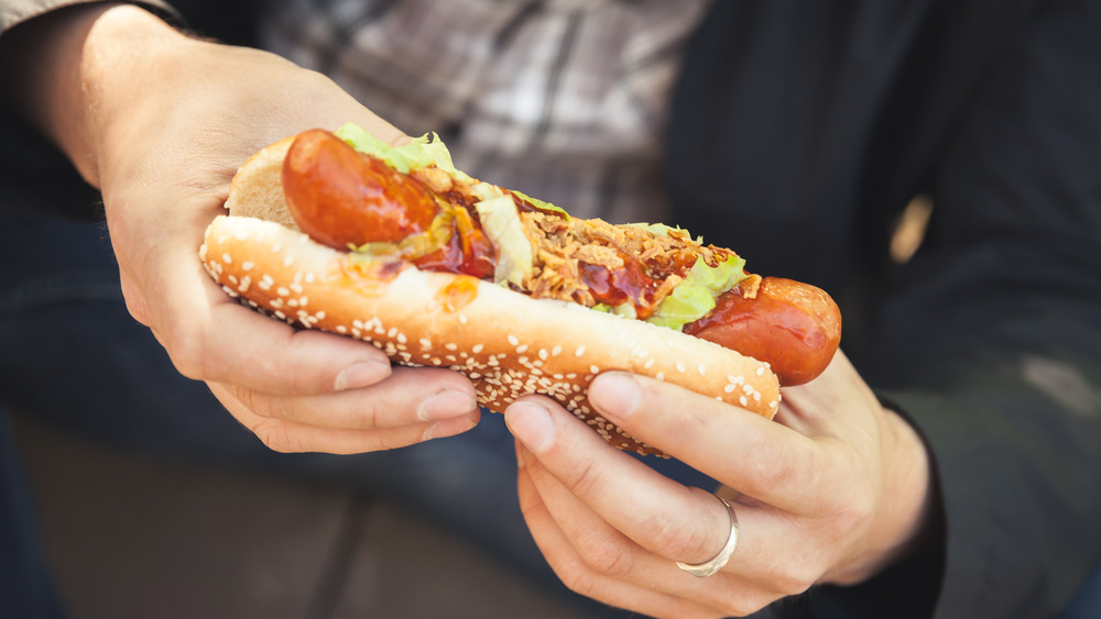 Hands holding hot dog
