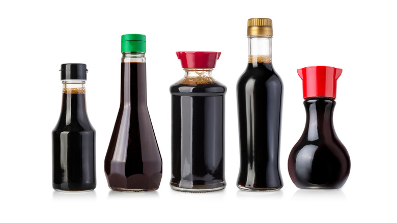 Bottles of soy sauce on white background