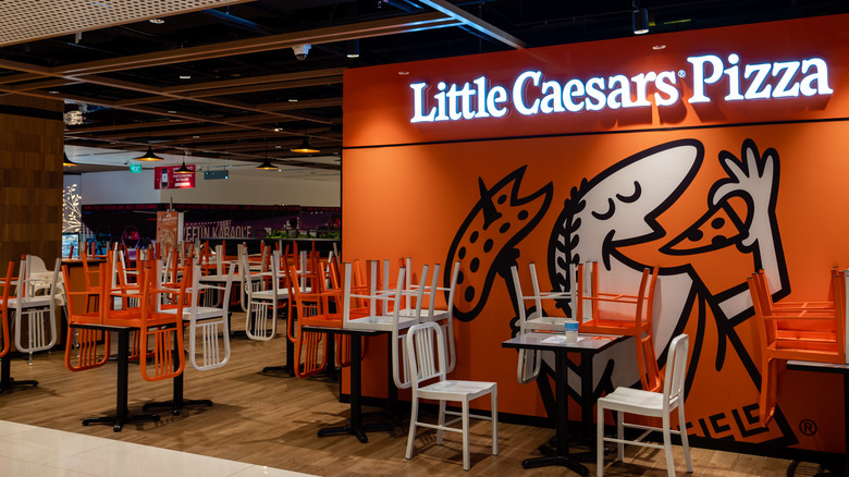 Inside a Little Caesars restaurant with chairs on tables