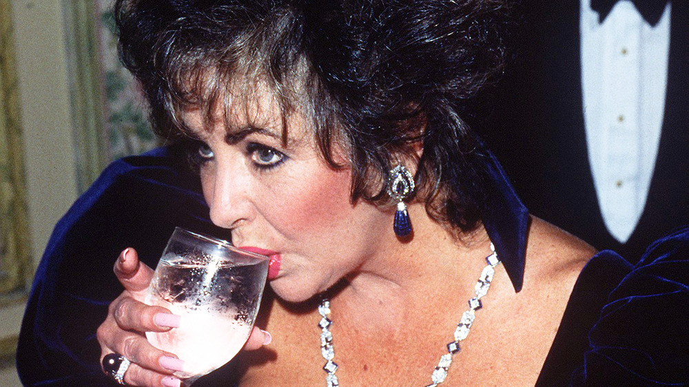 Elizabeth Taylor drinking something from a glass
