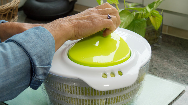 a woman using a salad spinner on the kitchen countertop