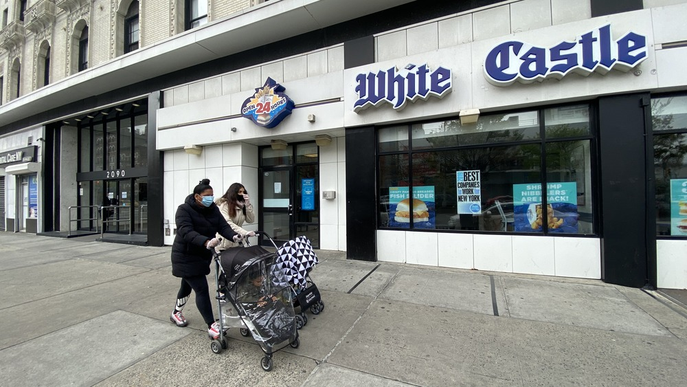 People wearing face masks walk in front of a White Castle
