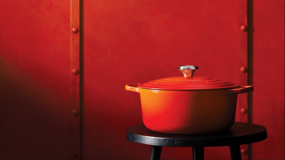 """Le Creuset dutch oven in classic """"flame"""" color set against a red-orange background."""