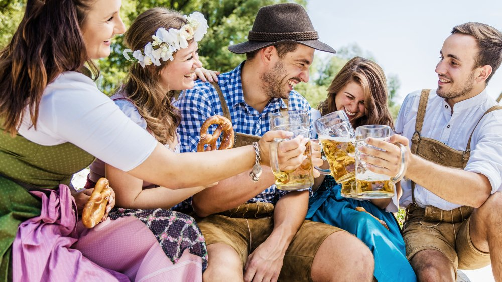 people dressed to celebrate Oktoberfest with pints of beer