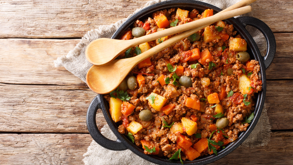 Cuban picadillo in a bowl with wooden spoons, on wooden table