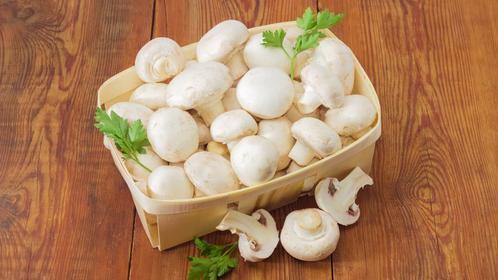 White button mushrooms in a basket