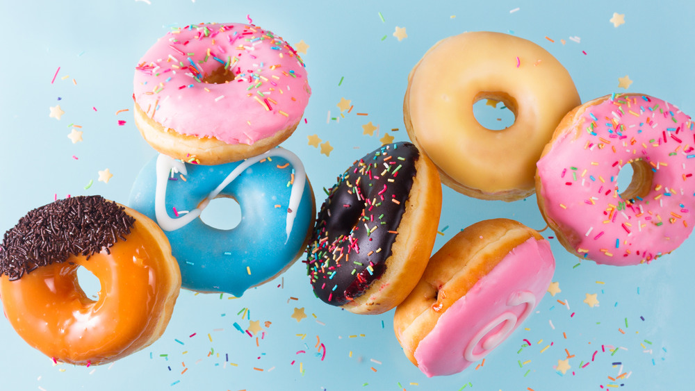 Colorful doughnuts and sprinkles on a blue background