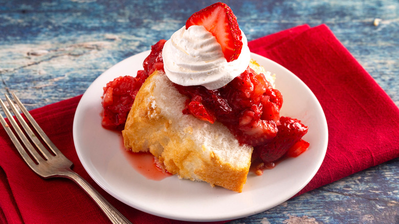 Strawberry shortcake with whipped cream and red napkin