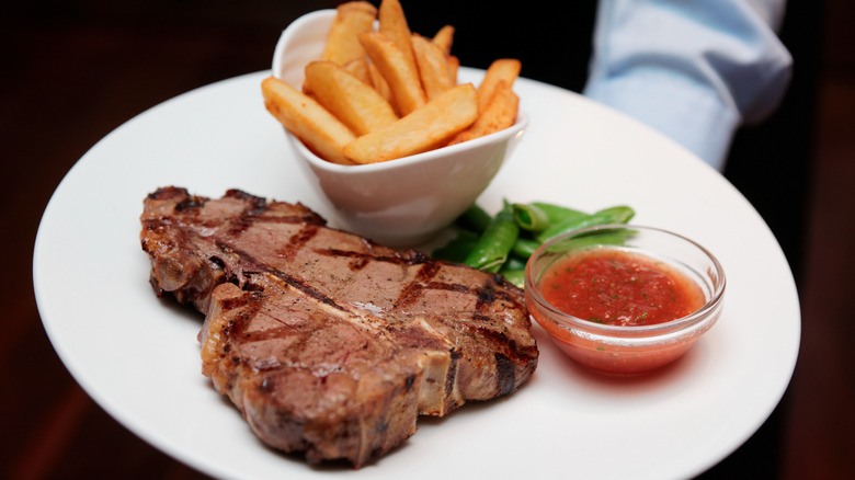Waiter holding T-bone and french fries on a plate