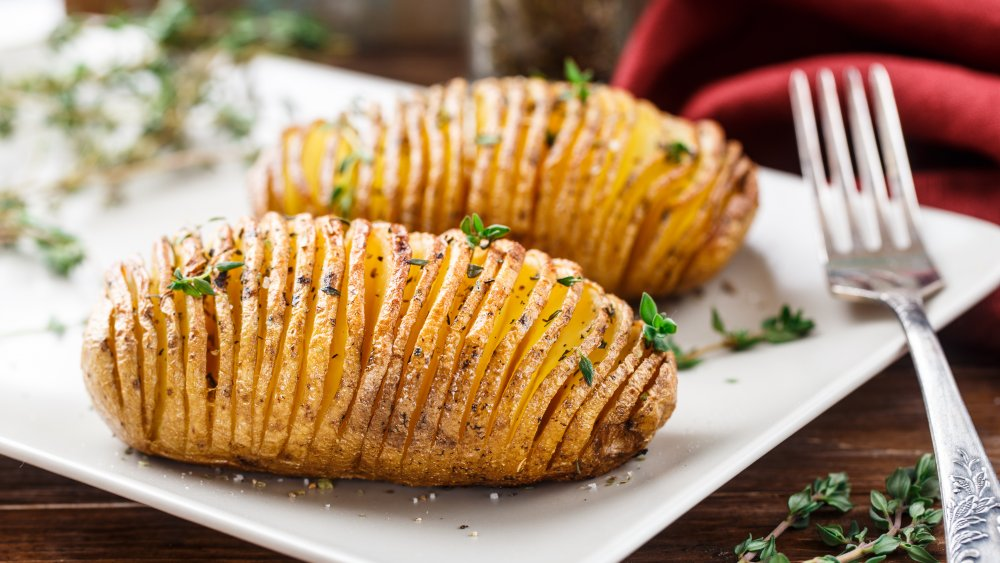 Hasselback potatoes on white plate with fork