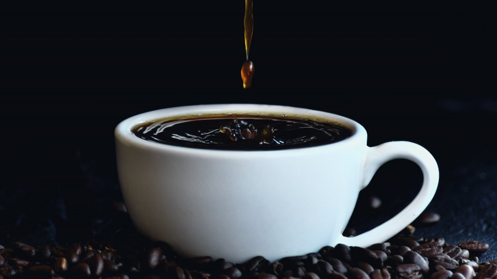 Cup of coffee pouring with coffee beans