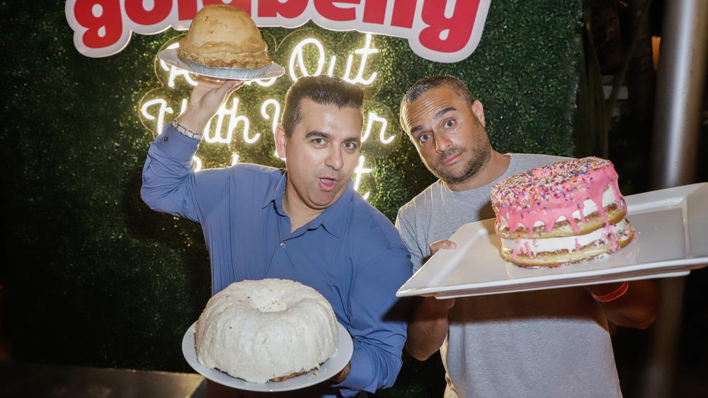 Buddy Valastro and Joe Ariel holding cakes in front of Goldbelly sign