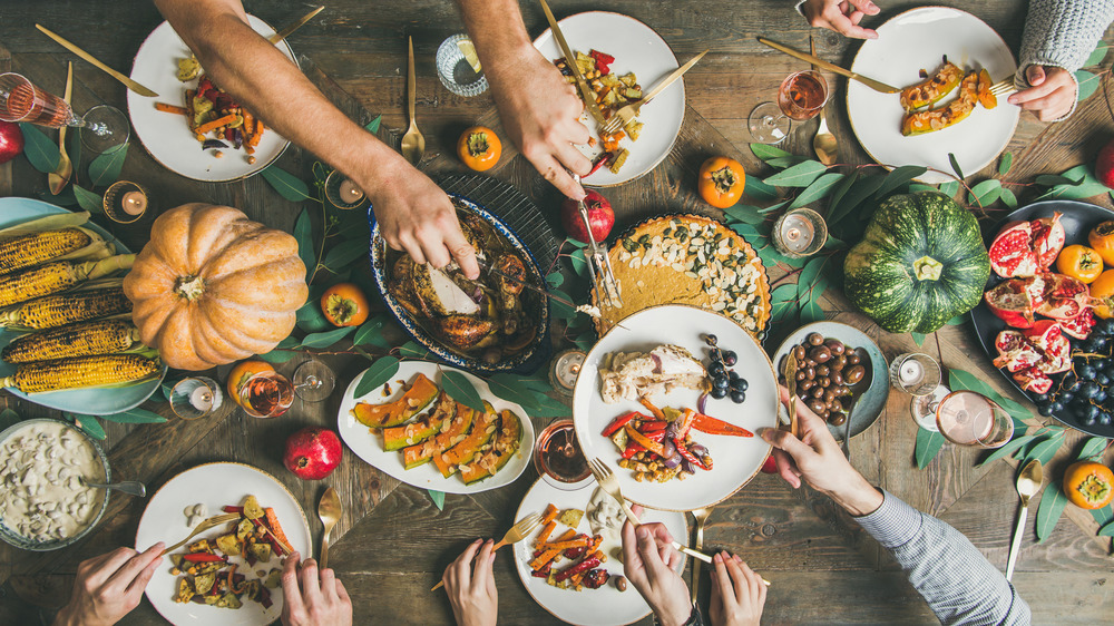 Thanksgiving table with turkey and sides, hands sharing