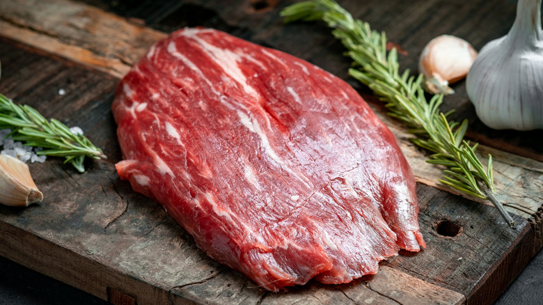 Raw flank steak on cutting board with rosemary