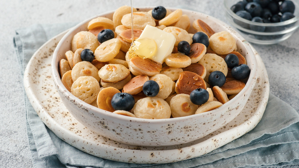 Pancake cereal with honey, butter, and blueberries