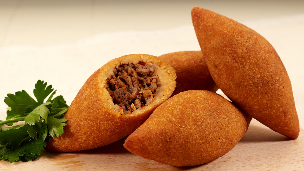 A pile of kibbeh with one open