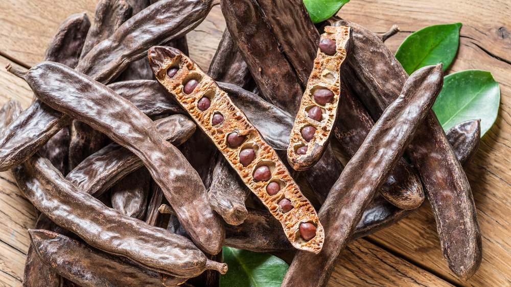 Carob pods on wooden surface