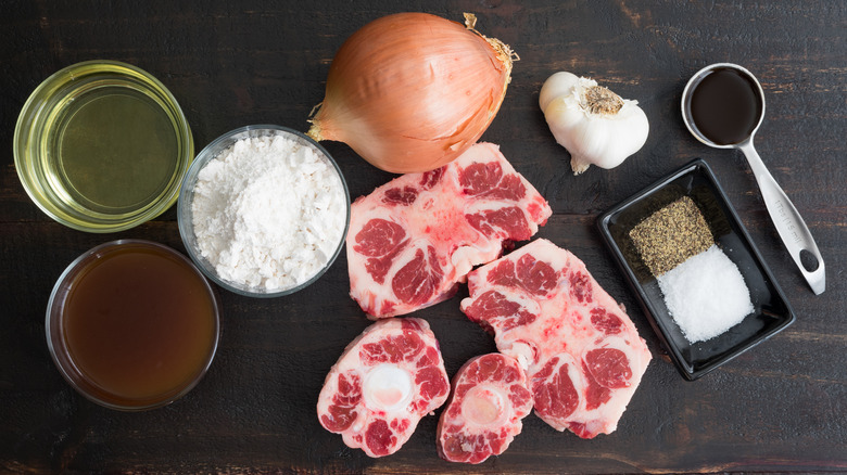 Raw oxtail and ingredients on a dark table