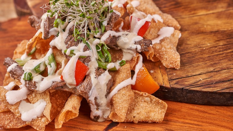 Pile of nachos with beef, sprouts, and cream on wood table