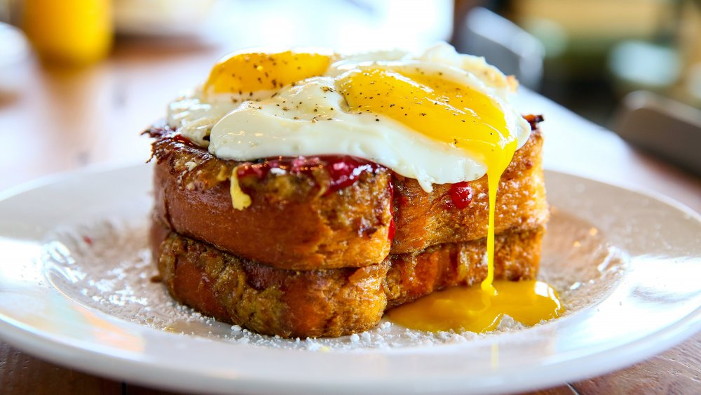 Stack of French toast topped with two runny, fried eggs.