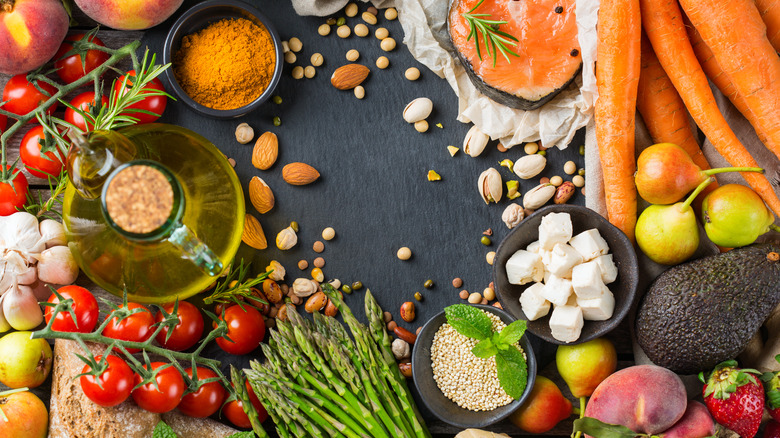 Array of Mediterranean food items including carrots, feta cheese, tomato, almonds, avocado, and asparagus