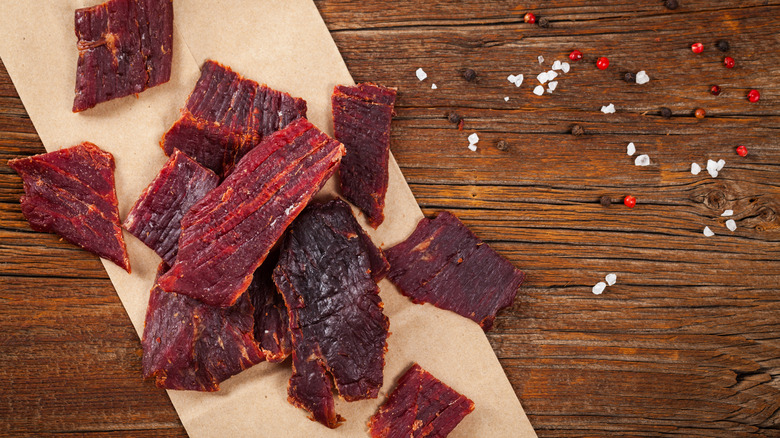pieces of beef jerky on wood background