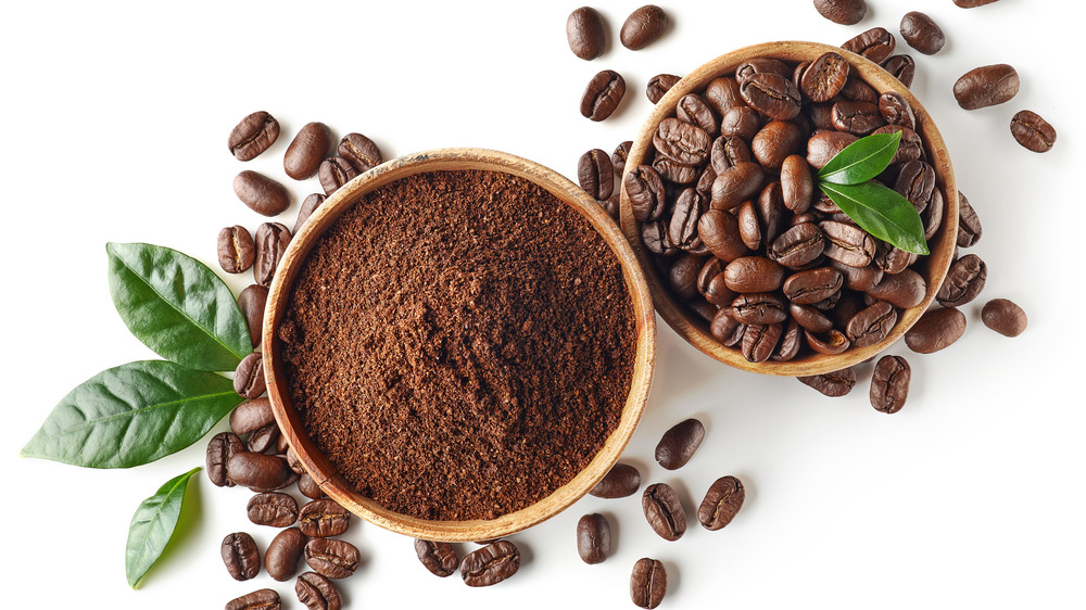 Coffee grounds in bowl with beans