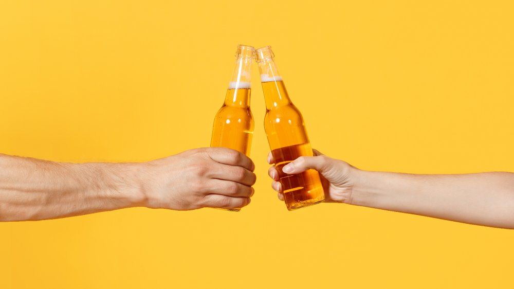 two people with beer bottles
