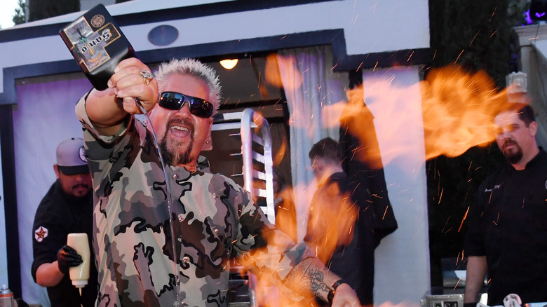 Guy Fieri cooking over fire.