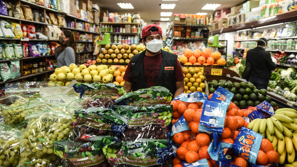Bodega worker surrounded by veggies