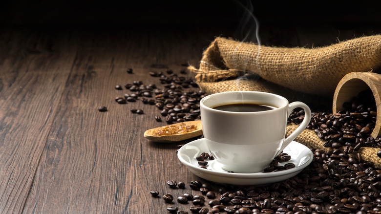 Hot cup of coffee with coffee beans on dark table
