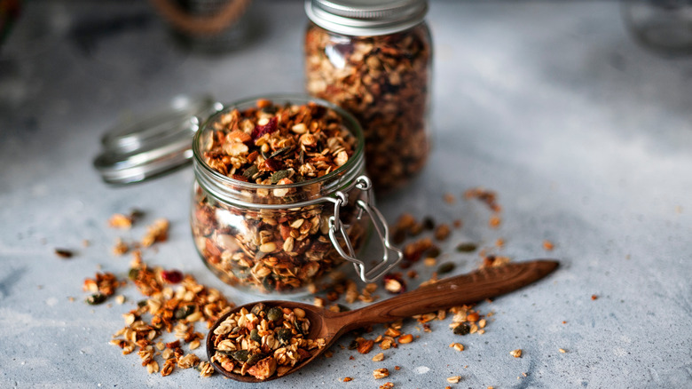 two jars of granola and wooden spoon