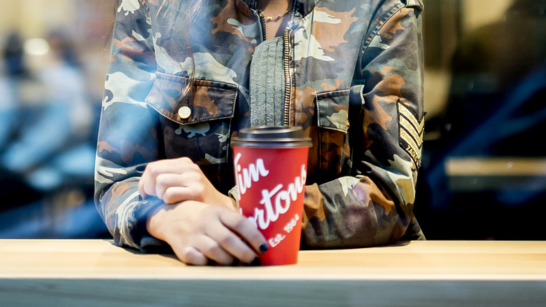 Person drinking Tim Hortons coffee