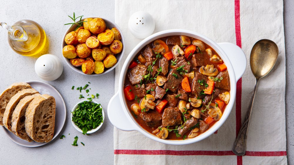 pot of beef stew with bread and potatoes