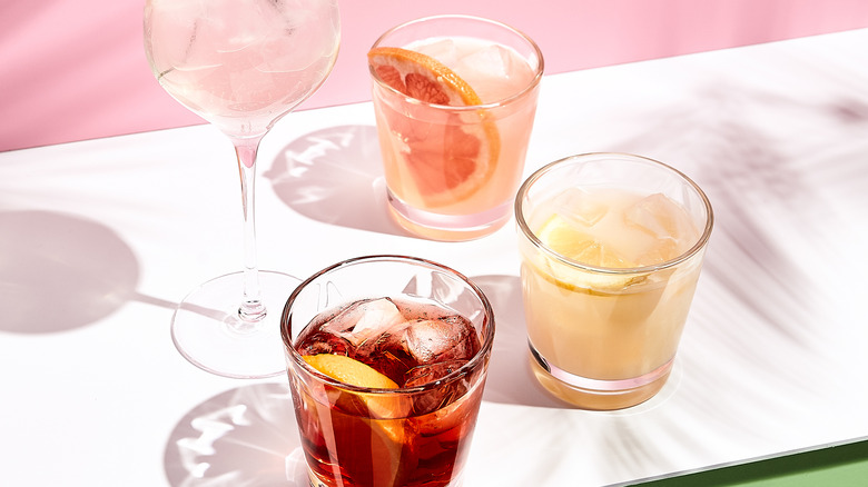 Four cocktails on pink background