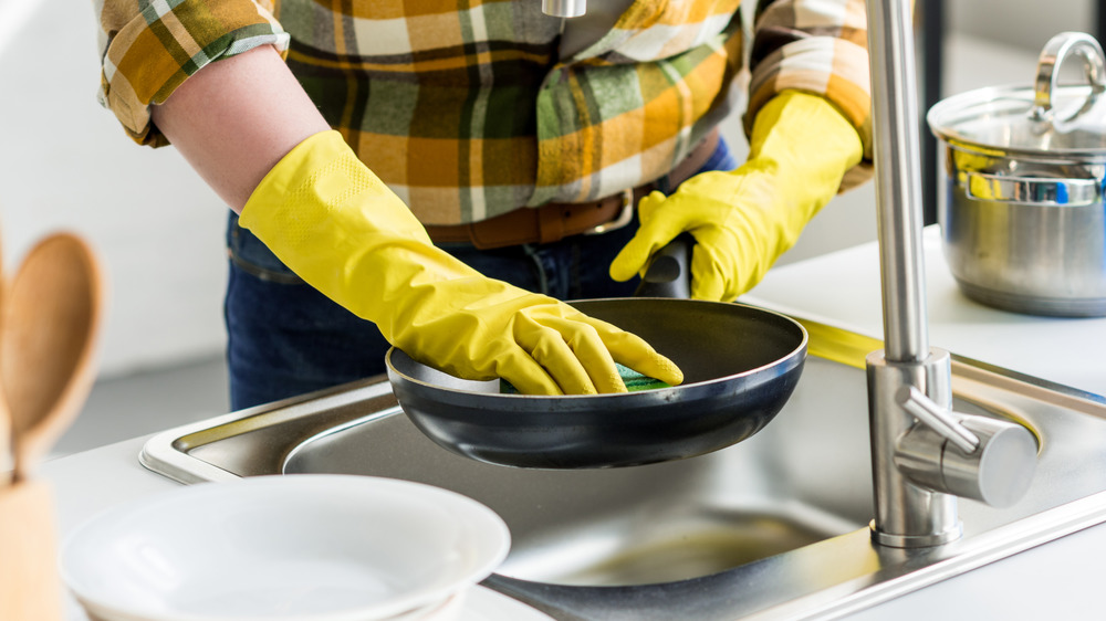 Person cleaning pan with gloves